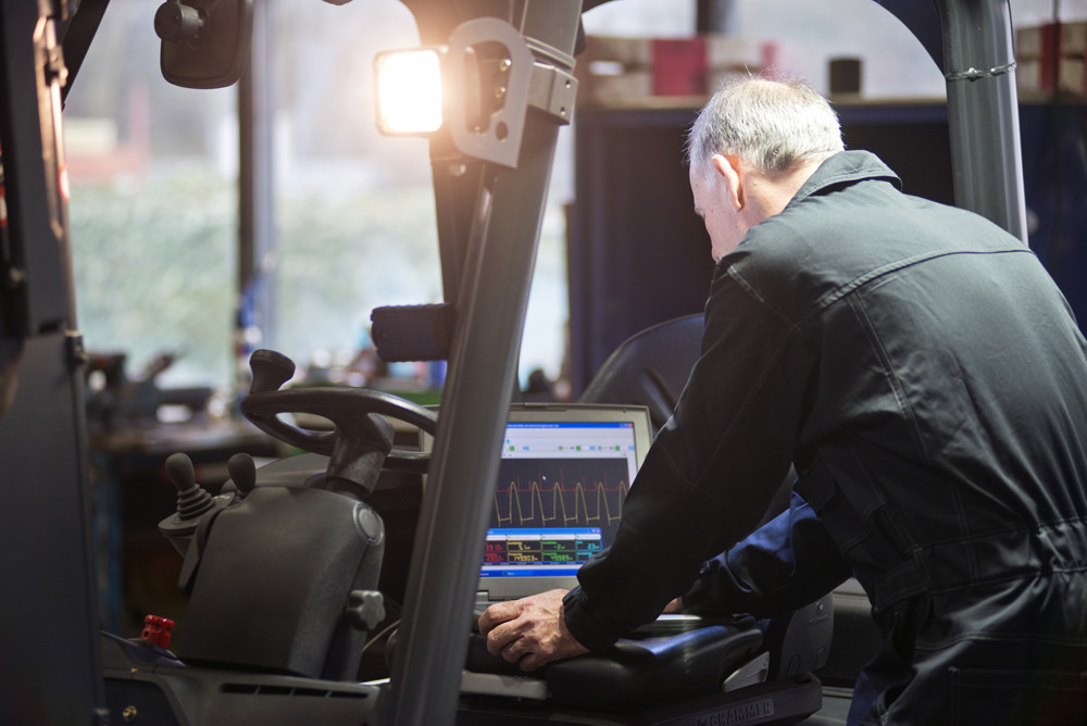 Man on Computer with Forklift in background